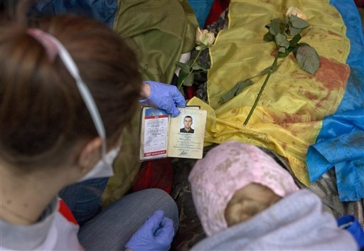 A paramedic looks at the identification document of a killed anti-government protester, in central Kiev, Ukraine, Thursday, Feb. 20, 2014. A brief truce in Ukraine's embattled capital failed Thurs ...
