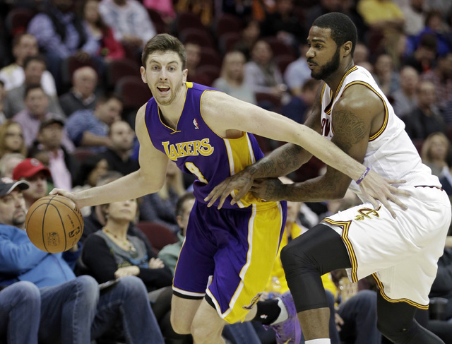 Los Angeles Lakers' Ryan Kelly, left, tries to drive around Cleveland Cavaliers' Earl Clark in the second quarter of an NBA basketball game on Wednesday, Feb. 5, 2014, in Cleveland. (AP Photo/Mark ...