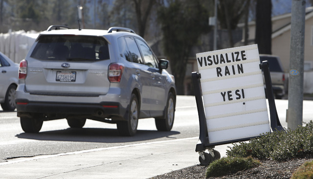 In this photo taken Tuesday, Feb. 4, 2014,  a sign outside a market in Willits, Calif., reminds passerby's about about the short water supply facing area residents. In the midst of a historic drou ...