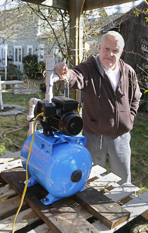 In this photo taken Tuesday, Feb. 4, 2014, Charles Davison, a retired high school principal, installed a pump on a unused well on to help supplement his household water supply at his home in Willi ...