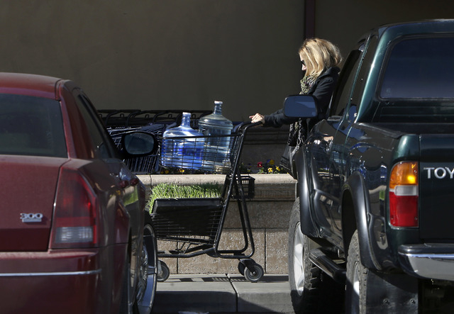 In this photo taken Tuesday, Feb. 4, 2014,  Kathleen Camp leaves a local market with bottled water in Willits, Calif.  With area reservoirs holding less than a 100-day supply of water, city leader ...