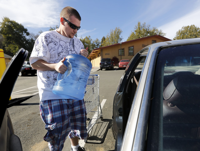 In this photo taken Tuesday, Feb. 4, 2014, Forrest Clark, 25, loads five gallon bottles of water, purchased at a local store, into his car in Willits, Calif.  With local reservoirs holding less th ...