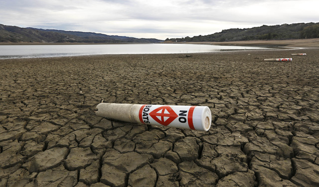 In this photo taken Tuesday, Feb. 4, 2014, a warning buoy sits on the dry, cracked bed of Lake Mendocino near Ukiah, Calif.  Despite recent spot rains The reservoir is currently only about 37 perc ...
