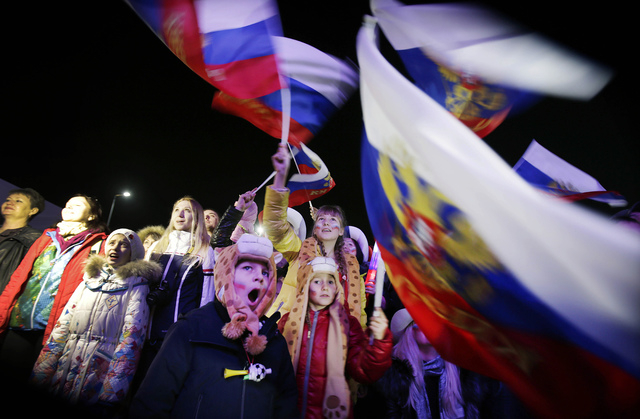 A Russian child yawns while others wave the national flag as the Russian national anthem is played during the live telecast of the 2014 Winter Olympics opening ceremony, Friday, Feb. 7, 2014, in d ...
