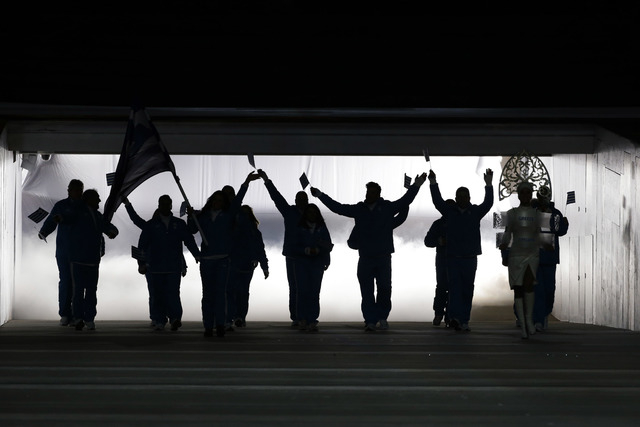 Athletes from Greece are silhouetted as they arrive during the opening ceremony of the 2014 Winter Olympics in Sochi, Russia, Friday, Feb. 7, 2014. (AP Photo/Mark Humphrey)