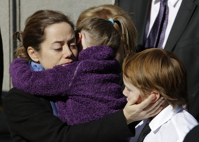 Mimi O'Donnell, estranged partner of actor Philip Seymour Hoffman, comforts two of their children, daughter Willa, and son Cooper as his casket arrives at the Church of St. Ignatius Loyola, Friday ...
