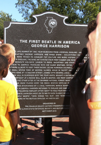 This photo taken on Sept. 21, 2013, shows residents in Benton, Ill., reading a historical marker honoring late Beatles guitarist George Harrison's visit 50 years earlier to Benton, Ill., where he  ...
