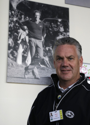 Steve John, CEO of the Monterey Peninsula Foundation and tournament director of the AT&T Pebble Beach Pro-Am golf tournament, poses beneath a photograph of Clint Eastwood Friday, Feb. 7, 2014, in  ...