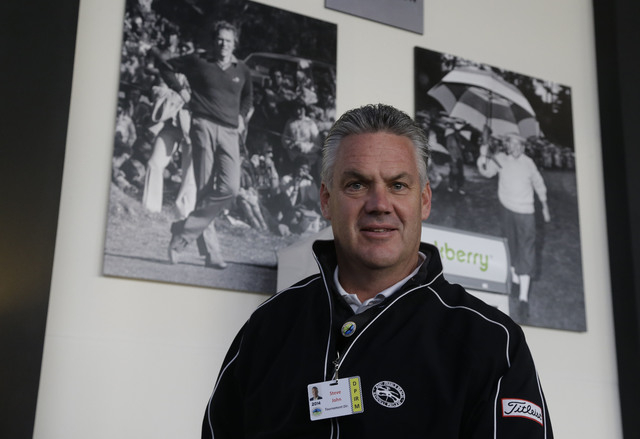 Steve John, CEO of the Monterey Peninsula Foundation and tournament director of the AT&T Pebble Beach Pro-Am golf tournament, poses beneath photographs of Clint Eastwood, left, and Bing Crosby, ri ...