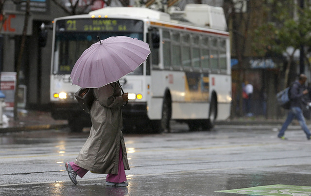 A woman carries an umbrella as she crosses Market Street in San Francisco, Saturday, Feb. 8, 2014. Californians accustomed to complaining about the slightest change in the weather welcomed a robus ...