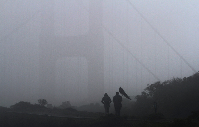 A gust of wind gets the better of an umbrella carried by a visitor to Battery Spencer, overlooking the Golden Gate Bridge, in Sausalito, Calif. on Saturday, Feb. 8,  2014. (AP Photo/ Marin Indepen ...