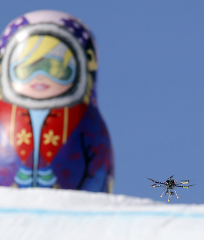 In this Friday Feb. 7 photo, a drone camera  flies about the slopestyle course during a freestyle skiing slopestyle training session at the Rosa Khutor Extreme Park ahead of the 2014 Winter Olympi ...