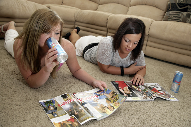 Megan Ward, left, drinks an energy drink with her friend Mykel Prescott from Parker, Colo., at Ward's home in Castle Rock, Colo. The journal Pediatrics published online Monday the results of resea ...