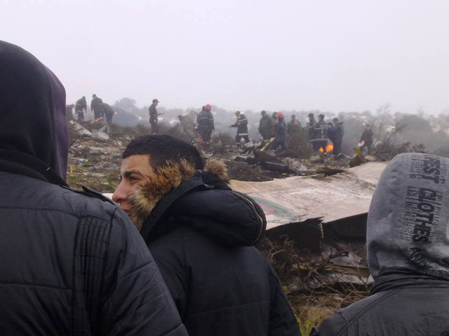People watch rescue workers working at the wreckage of an Algerian military transport aircraft after it slammed into a mountain in the countrys rugged eastern region, Tuesday, Feb. 11, 2014. A civ ...