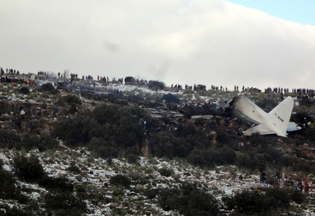 People look at the wreckage of Algerian military transport plane after it slammed into a mountain in the countrys rugged eastern region, Tuesday, Feb. 11, 2014. A civil defense official said 102 p ...