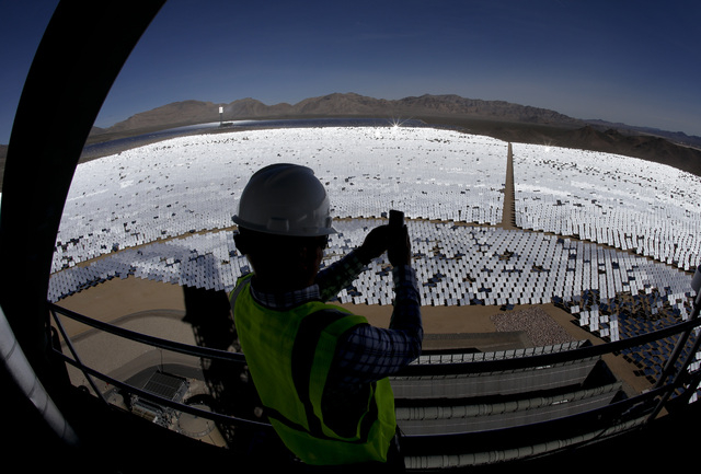 Jeff Holland takes a picture of some of the 300,000 computer-controlled mirrors that reflect sunlight to boilers that sit on 459-foot towers Tuesday, Feb. 11, 2014 in Primm, Nev. The Ivanpah Solar ...