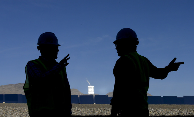 Jeff Holland, right, talks with Noel Hanson  near a boilers that sit on 459-foot towers Tuesday, Feb. 11, 2014 in Primm, Nev. The Ivanpah Solar Electric Generating System, sprawling across roughly ...