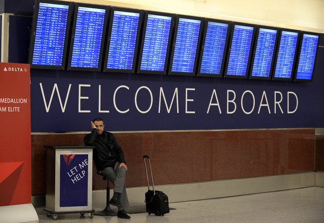 Airline passenger Hossam Shalaby from Egypt waits Tuesday for his rescheduled flight to Orlando under the departure board showing hundreds of cancellations at Hartsfield-Jackson International Airp ...