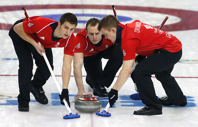 Britain's Michael Goodfellow, center, releases the rock while Scott Andrews, left, and Greg Drummond, right, sweep the ice during the men's curling competition against Denmark at the 2014 Winter O ...