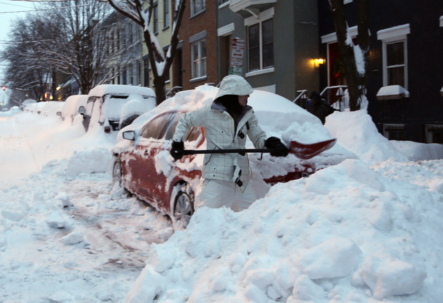 Liz Hall of Albany, N.Y., digs her car out of snow in the Center Square neighborhood on Friday in Albany. Schools are closed across eastern New York as the region starts to dig out from 12 to 20 i ...