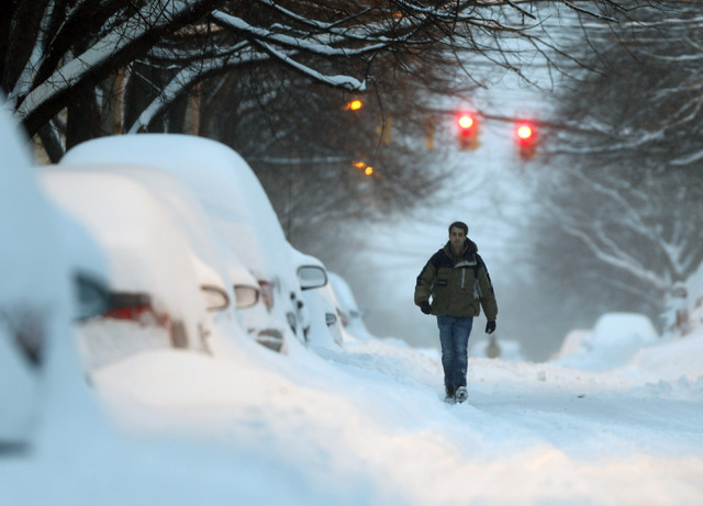 A pedestrian walks along a snow-covered street Friday in Albany, N.Y. Schools are closed across a swath of eastern New York as the region starts to dig out from 12 to 20 inches of snow dumped by t ...