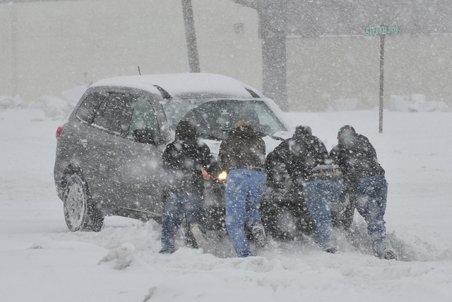 Good Samaritans help push a stranded motorist stuck in deep snow on Thursday in Bethlehem, Pa. A wide swath of Pennsylvania awoke Thursday to a fresh coating of snow and a forecast for much more t ...