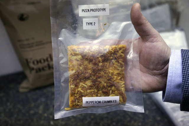 A packet containing a slice of prototype pizza is displayed by public affairs officer David Accetta at the U.S. Army Natick Soldier Research, Development and Engineering Center, in Natick, Mass. P ...