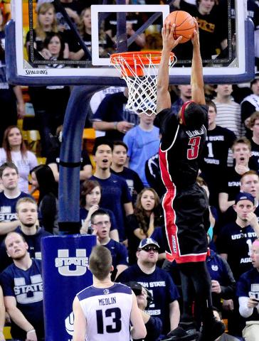 UNLV's Kevin Olekaibe (3) dunks the ball over Utah State's Preston Medlin during an NCAA college basketball game on Saturday, Feb. 15, 2014, in Logan, Utah. (AP Photo/Herald Journal, John Zsiray)