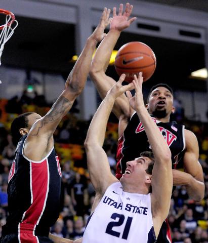 Utah State's Spencer Butterfield (21) has his shot blocked by UNLV's Bryce Dejean-Jones, left, and Khem Birch during an NCAA college basketball game on Saturday, Feb. 15, 2014, in Logan, Utah. (AP ...