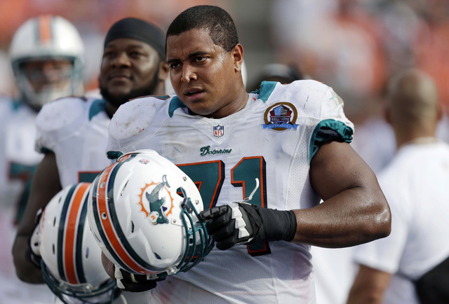 """Miami Dolphins tackle Jonathan Martin (71) watches from the sidelines during the second half of an NFL football game against the Jacksonville Jaguars, in Miami. Martin was subjected to """"a pattern  ..."""