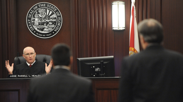 Judge Russell Healey, left rear, explains his answers to three related jury questions to defense attorney Cory Strolla, center, and defendant Michael Dunn, right, before bringing the jury into the ...