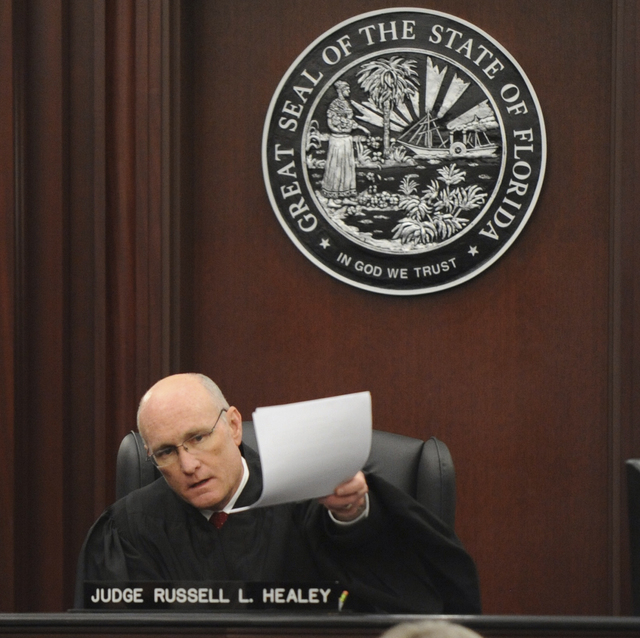 Judge Russell Healey holds up documents as he announces that the jury is deadlocked on charge one and have verdicts in the other four charges while deliberating, Saturday Feb. 15, 2014 in the tria ...