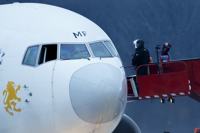 Police stand on the stairs after passengers were evacuated from a hijacked Ethiopian Airlines Plane Geneva's international airport on Monday. The  aircraft traveling from Addis Abeda, Ethiopia, to ...