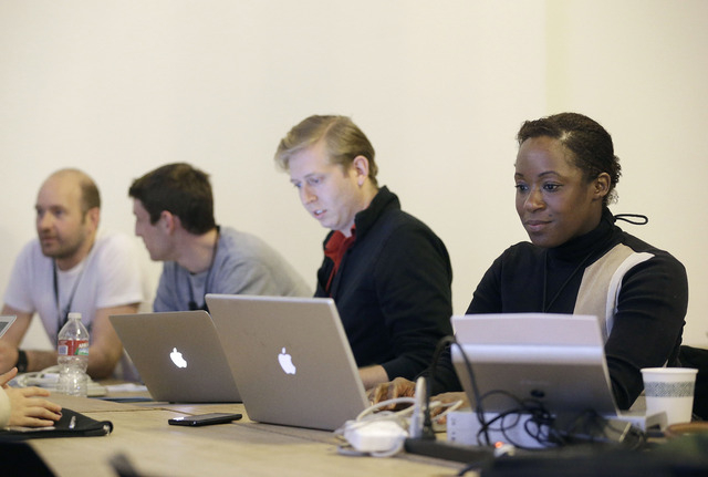 Fanya Young, right, and other participants work on their computers during a coding and team formation session at FinCapDev San Francisco Hackathon on Feb. 8 in San Francisco. (AP Photo/Jeff Chiu)