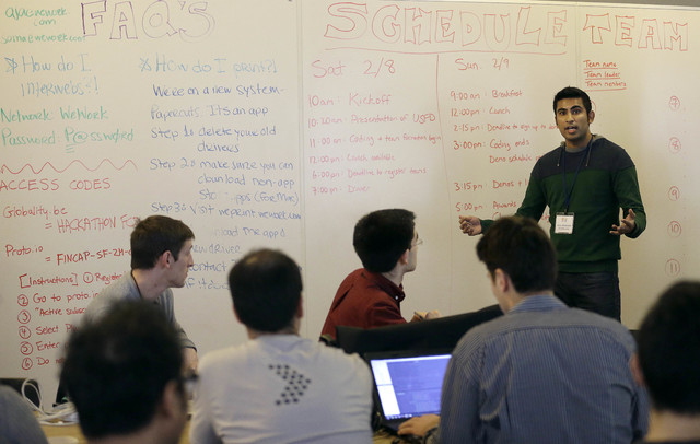 Karim Bhalwani, manager of API Strategy and Sales at Yodlee Interactive, right, speaks to participants at the FinCapDev San Francisco Hackathon on Feb. 8 in San Francisco.  (AP Photo/Jeff Chiu)