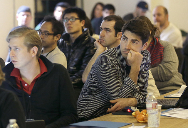 Segah Meer, right, and other participants listen to speakers during the FinCapDev San Francisco Hackathon on Feb. 8 in San Francisco. A record 1,500 hackathons around the world are planned for thi ...