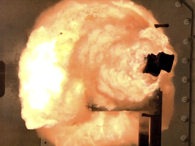 A high-speed camera captures the first full-energy shots from an electromagnetic launcher at a test facility in Dahlgren, Va., in 2012. (AP Photo/U.S. Navy, John F. Williams)