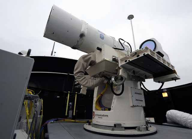 A laser weapon sits temporarily installed aboard the guided-missile destroyer USS Dewey in San Diego in 2012. The Navy plans to deploy its first laser on a ship in 2014, and intends to test an ele ...