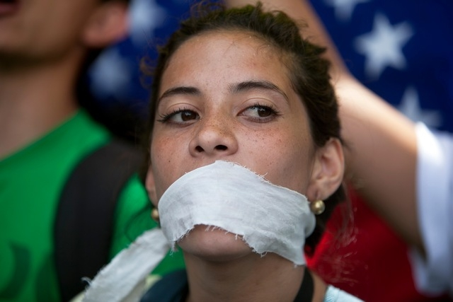 A demonstrator covers her mouth with a rag to prostest government censorship, during a march to Venezuelan Telecommunications Regulator Office or CONATEL in Caracas, Venezuela, Monday, Feb17, 2014 ...