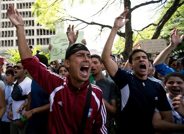 Students shout slogans against Venezuela's President Nicolas Maduro during a march to Venezuelan Telecommunications Regulator Office or CONATEL in Caracas, Venezuela, Monday, Feb17, 2014. The stud ...