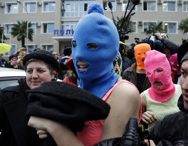 Russian punk group Pussy Riot members Nadezhda Tolokonnikova, in the blue balaclava, and Maria Alekhina, in the pink balaclava, make their way through a crowd after they were released from a polic ...