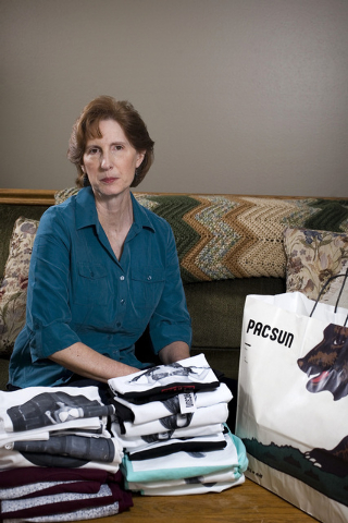 Judy Cox sits for a portrait next to a stack of T-shirts with what she believes are pornographic designs Monday, Feb. 17, 2014, in Orem, Utah. Cox purchased the entire stock of T-shirts for $567 f ...