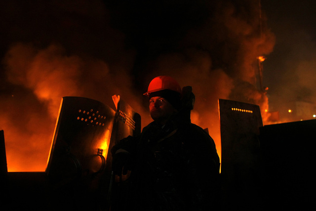 An anti-government protester mans a barricade at Independence Square in Kiev, Ukraine, Thursday, Feb. 20, 2014. Ukraine's protest leaders and the president they aim to oust called a truce Wednesda ...