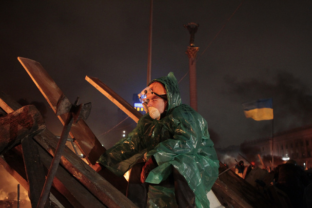 An anti-government protester guards the barricade in front of riot police in Kiev's Independence Square, the epicenter of Ukraine's current unrest. (AP Photo/Sergei Chuzavkov)