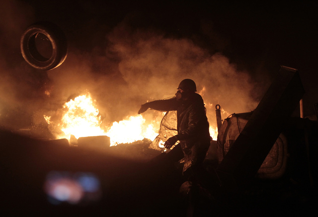 Anti-government protesters clash with riot police in Kiev's Independence Square, the epicenter of Ukraine's current unrest, Thursday. (AP Photo/Sergei Chuzavkov)
