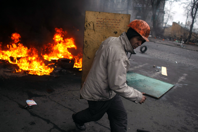 An anti-government protester carries a shield as he runs on the outskirts of Independence Square in Kiev, Ukraine, Thursday. Fierce clashes between police and protesters, some including gunfire, s ...