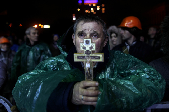 An anti-government protester holds a crucifix as he prays at Independence Square in Kiev, Ukraine, Thursday. Ukraine's protest leaders and the president they aim to oust called a truce Wednesday,  ...