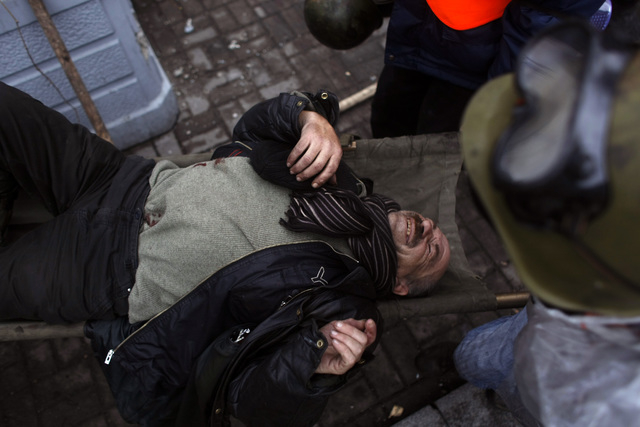 An injured anti-government protester is carried away to get treatment on the outskirts of Independence Square in Kiev, Ukraine, Thursday, Feb. 20, 2014. Fierce clashes between police and protester ...