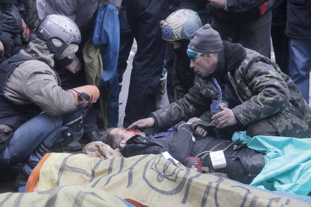 An activist closes a victim's eyes while others pay respects to protesters who were killed in clashes with police in Kiev's Independence Square, the epicenter of Ukraine's current unrest, on Thurs ...