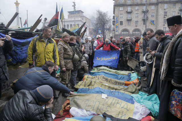 Activists and priests pay respects to protesters who were killed in clashes with police in Kiev's Independence Square, the epicenter of Ukraine's current unrest, on Thursday. A flag held by one ac ...